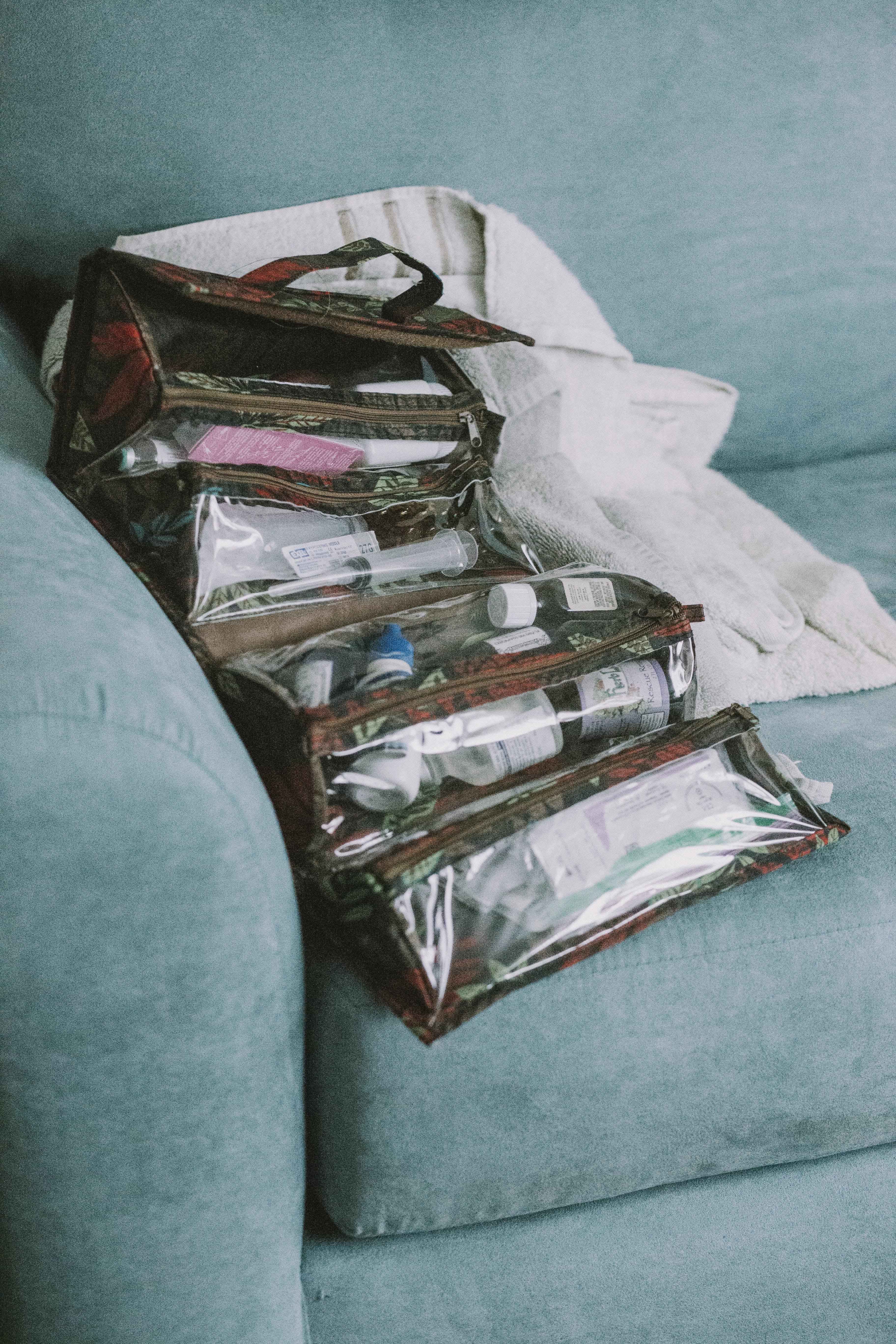 Items Inside Brown Hanging Organizer on Green Sofa