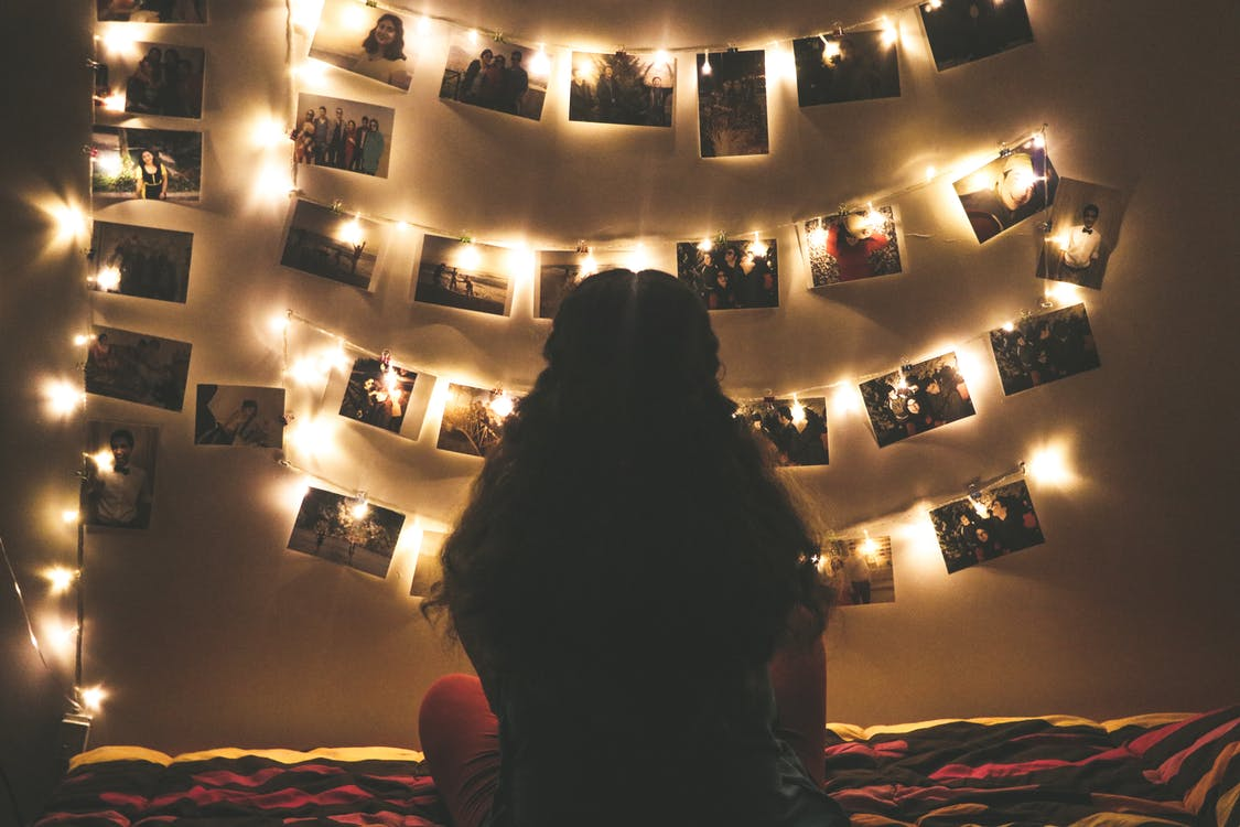 Woman Watching Photo Collection With String Lights