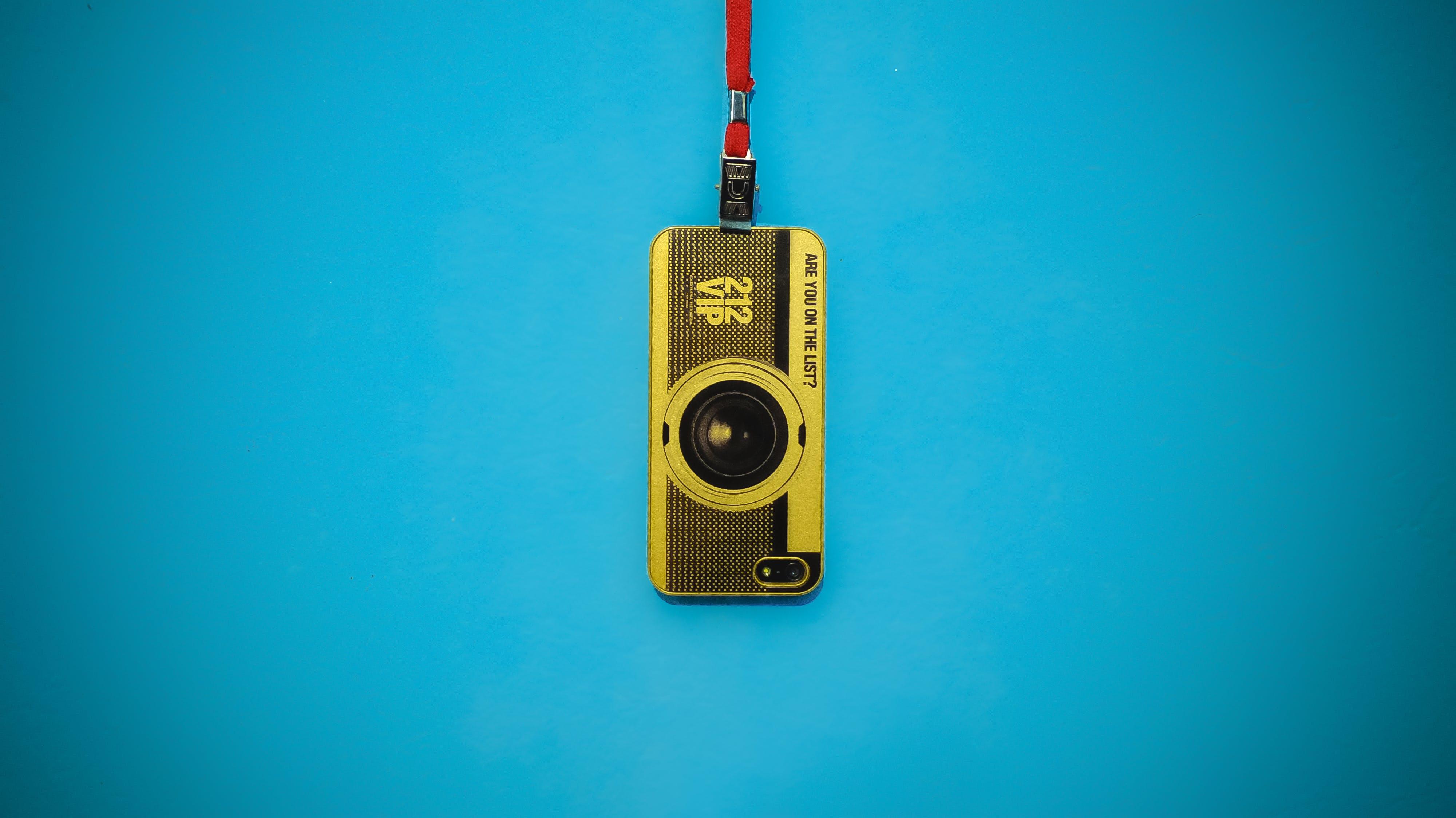 Yellow 212 Vip Camera Hanging on Blue Wall