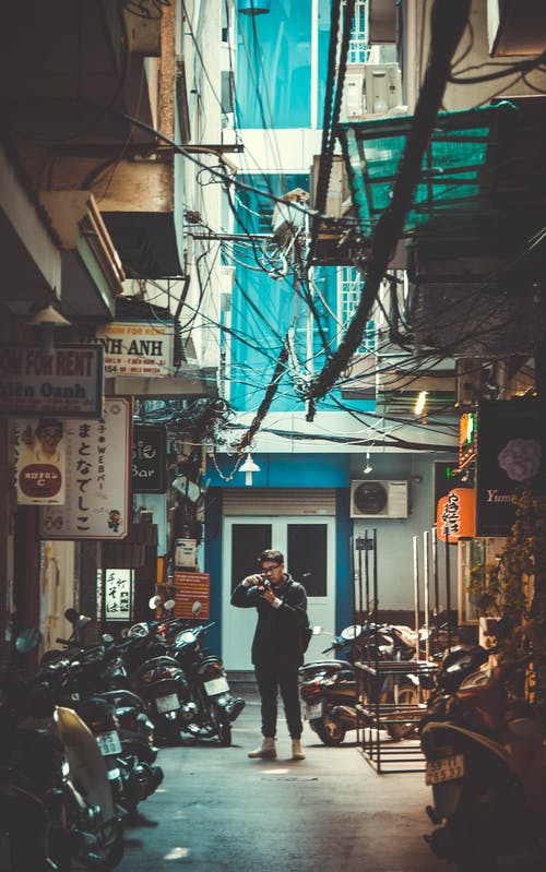 Man Standing on Concrete Road With Parked Motorcycles While Holding Dslr Camera