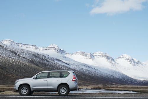 Gray Sports Utility Vehicle on Road Near Snow Covered Mountain