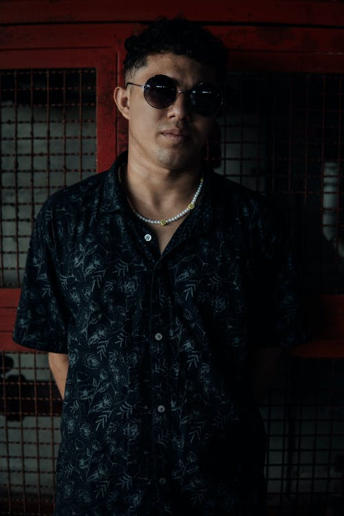 Man in a Black Floral Button Up Shirt Wearing Black Sunglasses