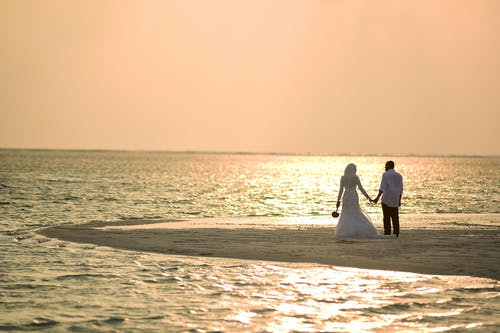Couple Holding Hands on Beach during Sunset
