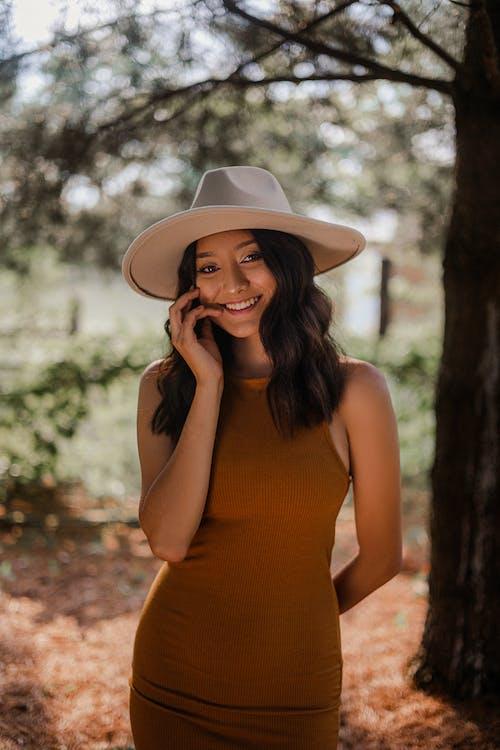 Woman in Orange Tank Top Wearing White Hat