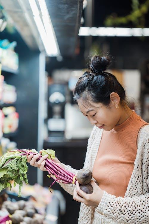 Женщина держит свеклу в супермаркете