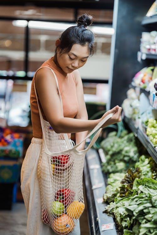 Женщина, покупающая продукты в супермаркете