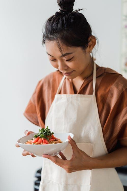 一个女人拿着一碗美味的意大利面