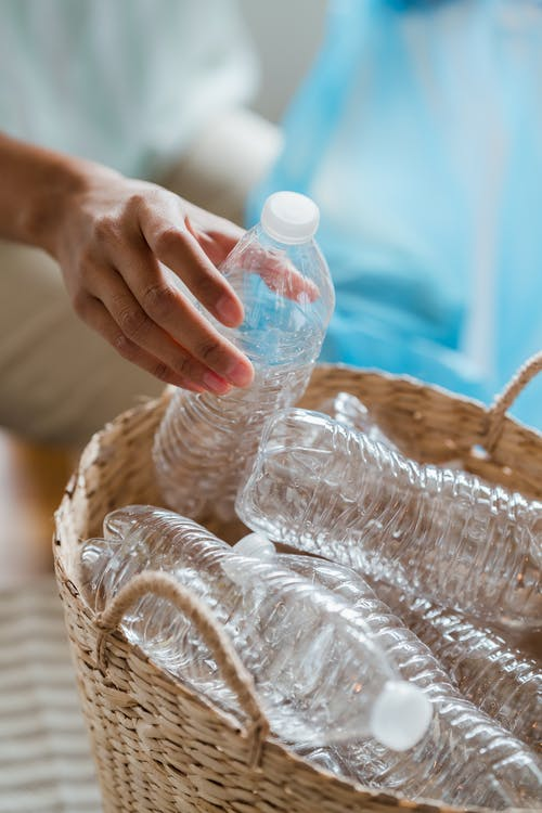 Person Putting Empty Plastic Bottles in a Basket