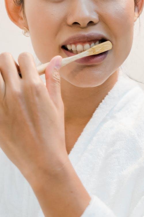 Woman in White Robe Holding Cigarette Stick