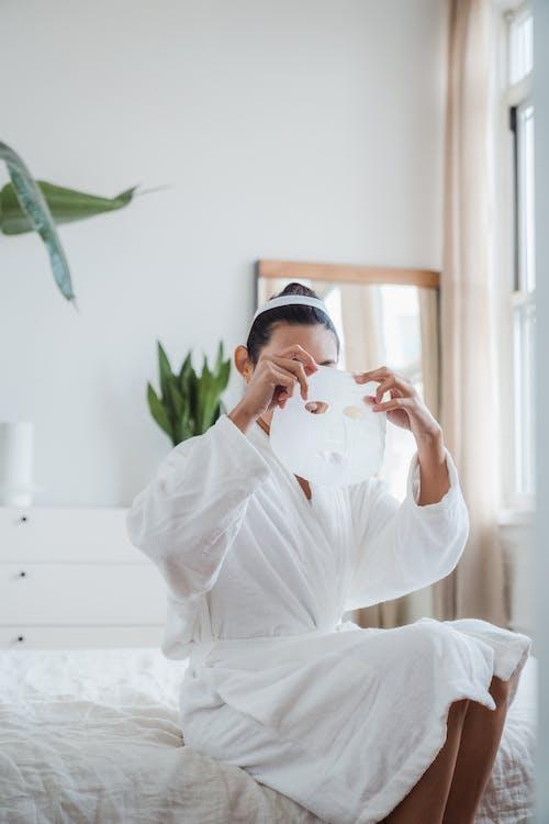Frau Im Weißen Bademantel, Die Eine Gesichtsmaske Aufsetzt
