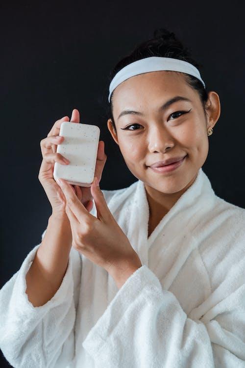 Smiling Woman in White Robe Holding White Ceramic Mug