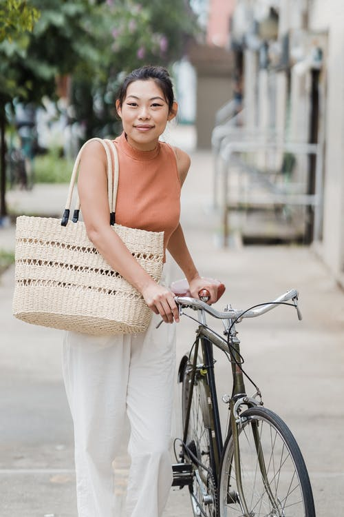 Woman in White Tank Top and White Pants Holding Brown Woven Basket