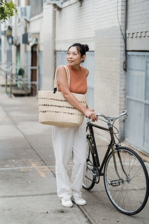 Woman in Pink Tank Top and White Pants Holding Black City Bike