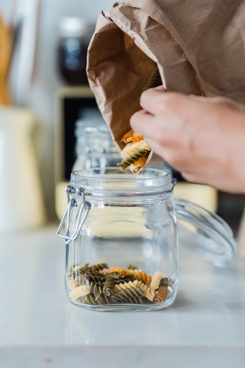 Person Holding Clear Glass Jar With Brown Liquid