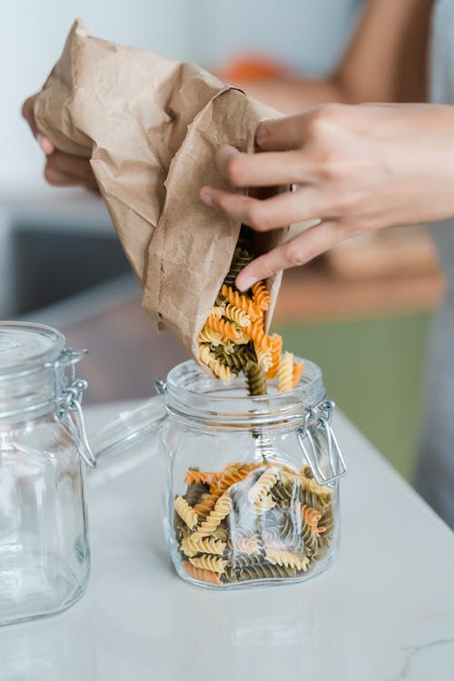 Person Holding Clear Glass Jar With Brown Dried Leaves