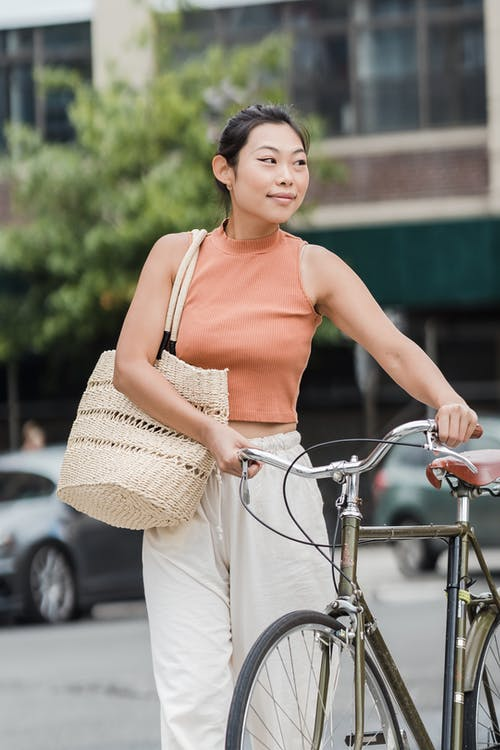 Woman in Orange Tank Top and Beige Skirt Holding Bicycle