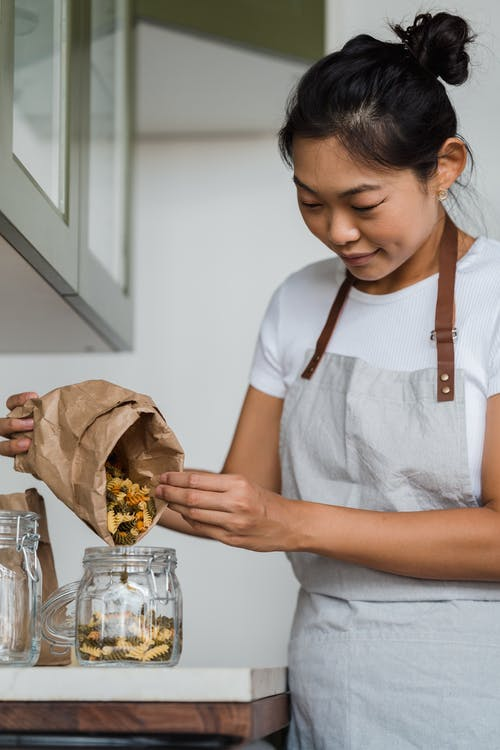 Woman Putting Uncooked Spiral Pasta in Clear Glass Jar