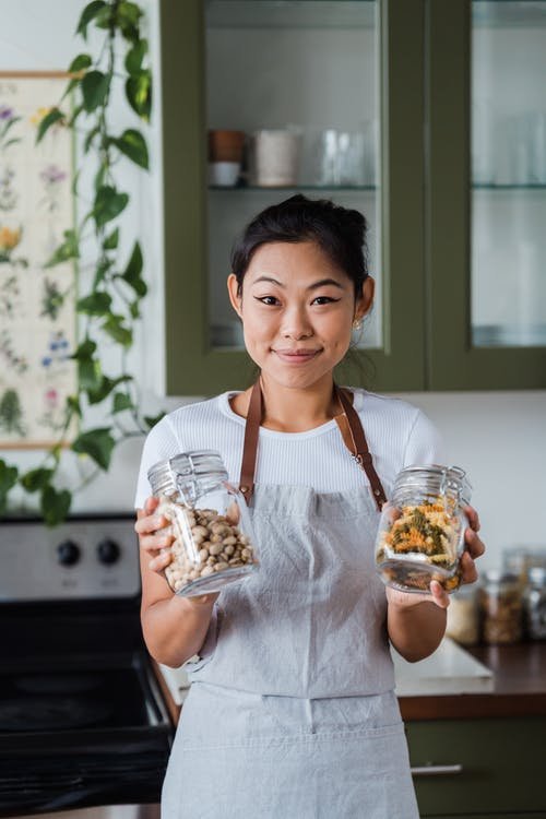 Woman Wearing an Apron while Holding Two Glass Jars
