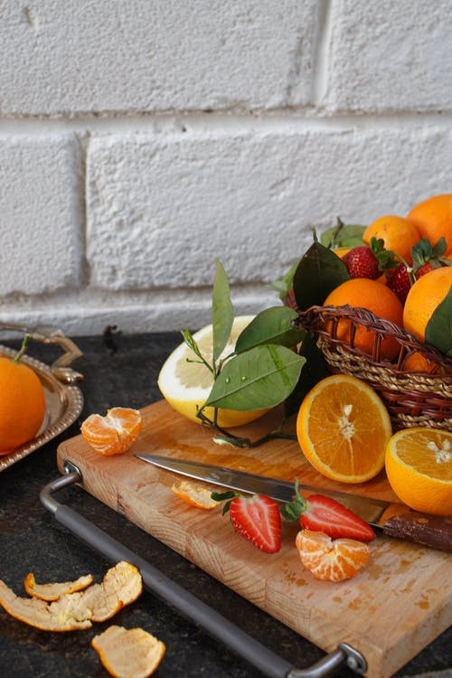 Orange Fruit on Brown Wooden Chopping Board