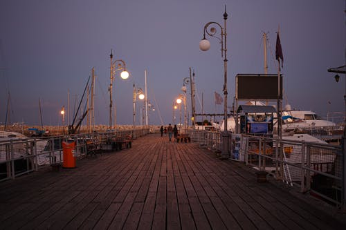 People Walking on Wooden Dock during Night Time