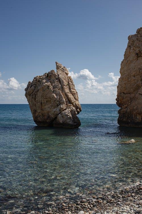 Brown Rock Formation on Blue Sea Under Blue Sky