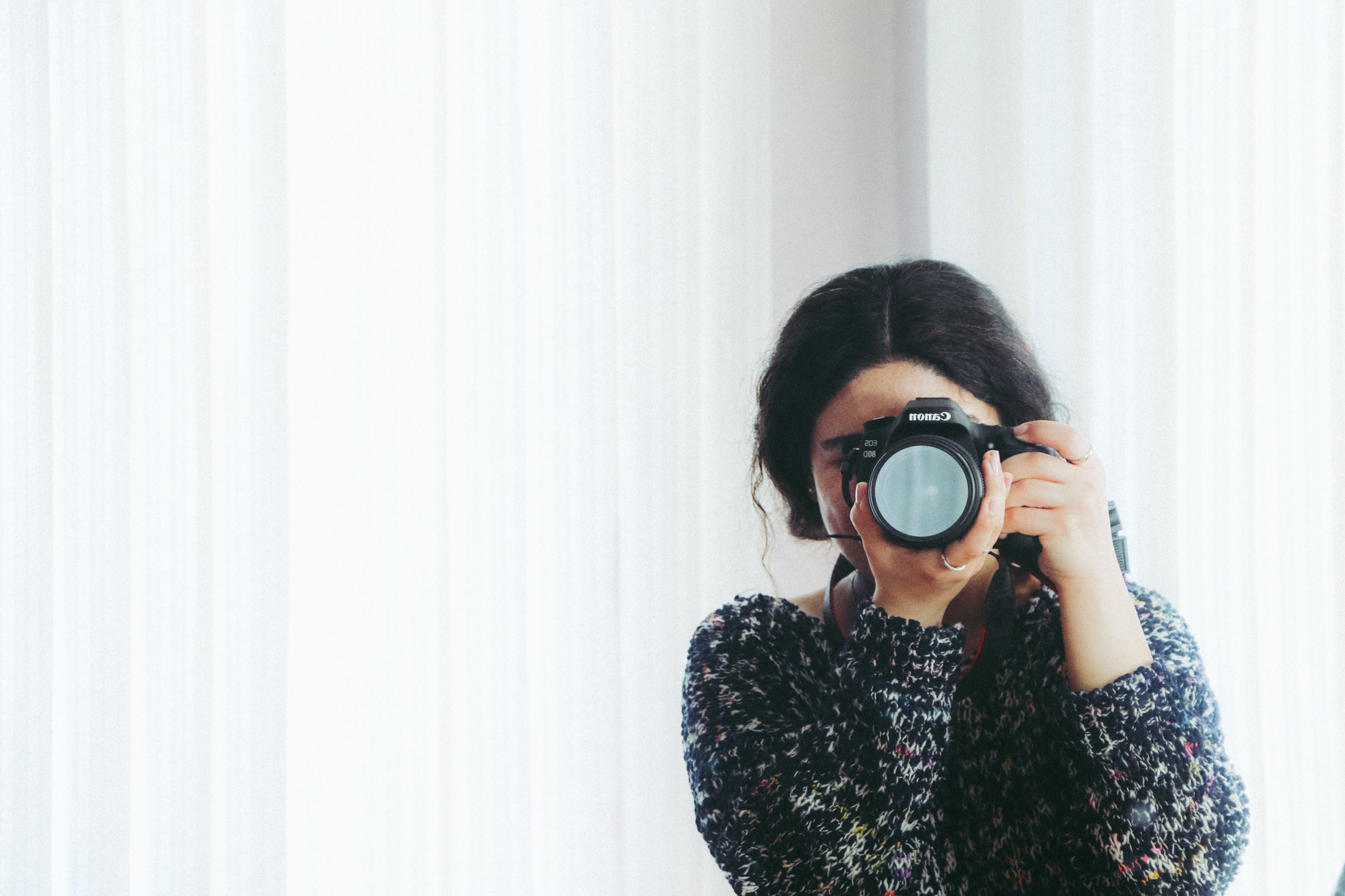 Woman in Black Long-sleeved Shirt Using Camera