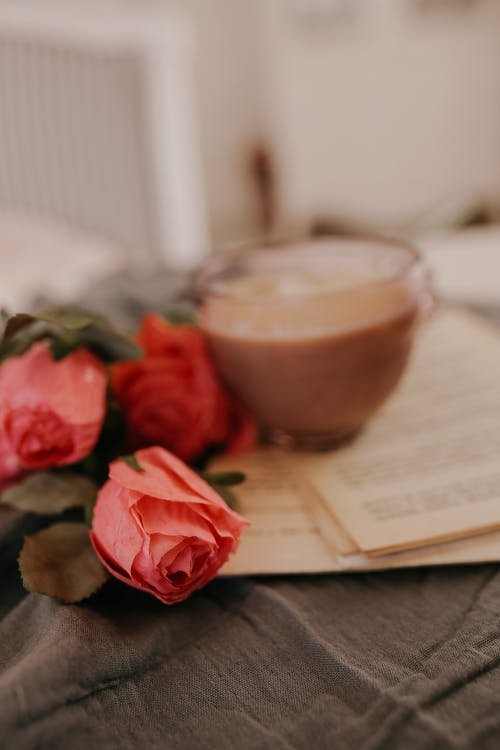 Pink Roses Beside White Ceramic Cup on White Paper