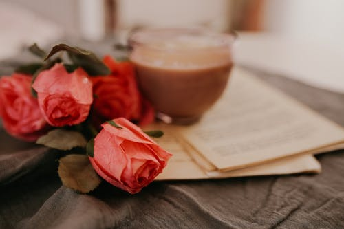 Red Rose Beside Brown Ceramic Cup on Brown Wooden Table