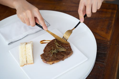 Person Slicing Meat on White Ceramic Plate