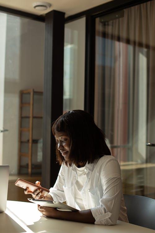 Photos gratuites de afro-américain, assis, en utilisant le téléphone