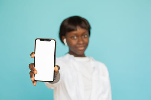 Woman in White Long Sleeve Shirt Holding White Iphone 5