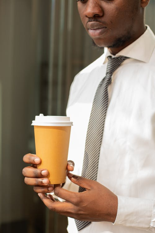 Man in White Dress Shirt Holding Yellow and White Disposable Cup