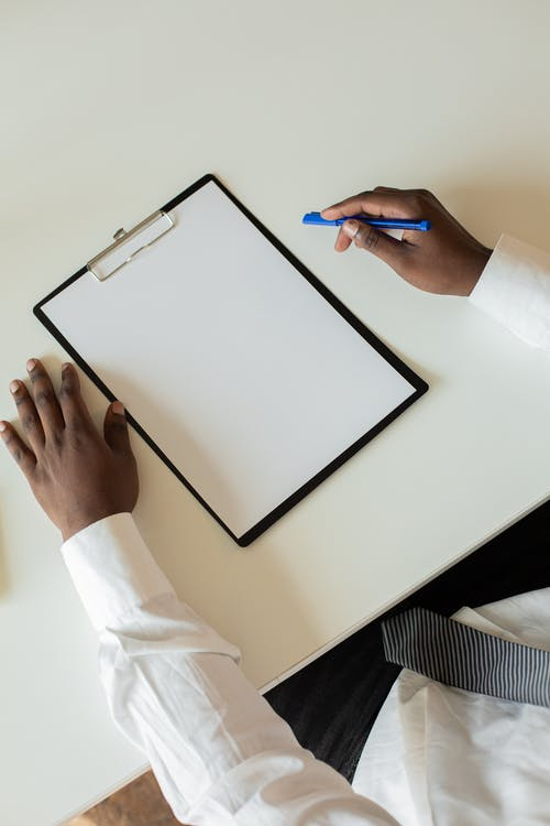 A Person with a Pen and a Blank Paper on a Clipboard