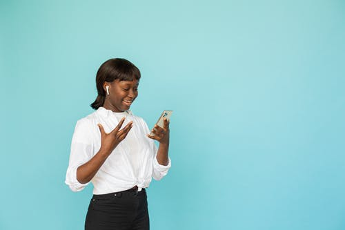 Woman in White Button Up Shirt and Black Pants Holding White Smartphone