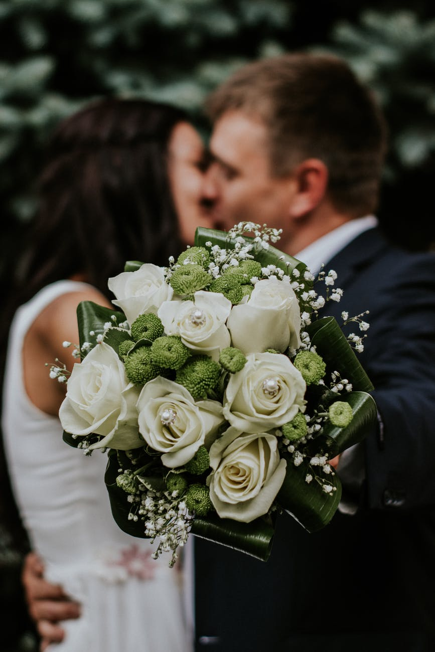 Groom and bride kissing on their wedding day.