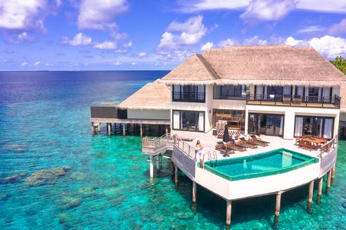 Brown Wooden House on Blue Sea Under Blue Sky