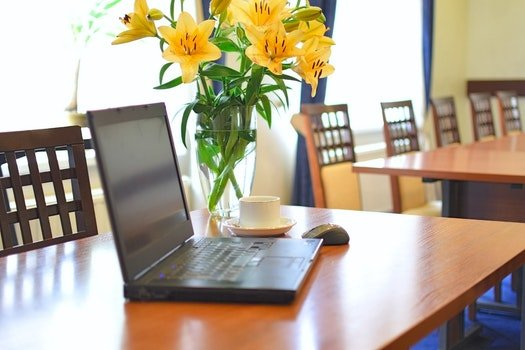 Laptop computer with coffee cup and vase of flowers