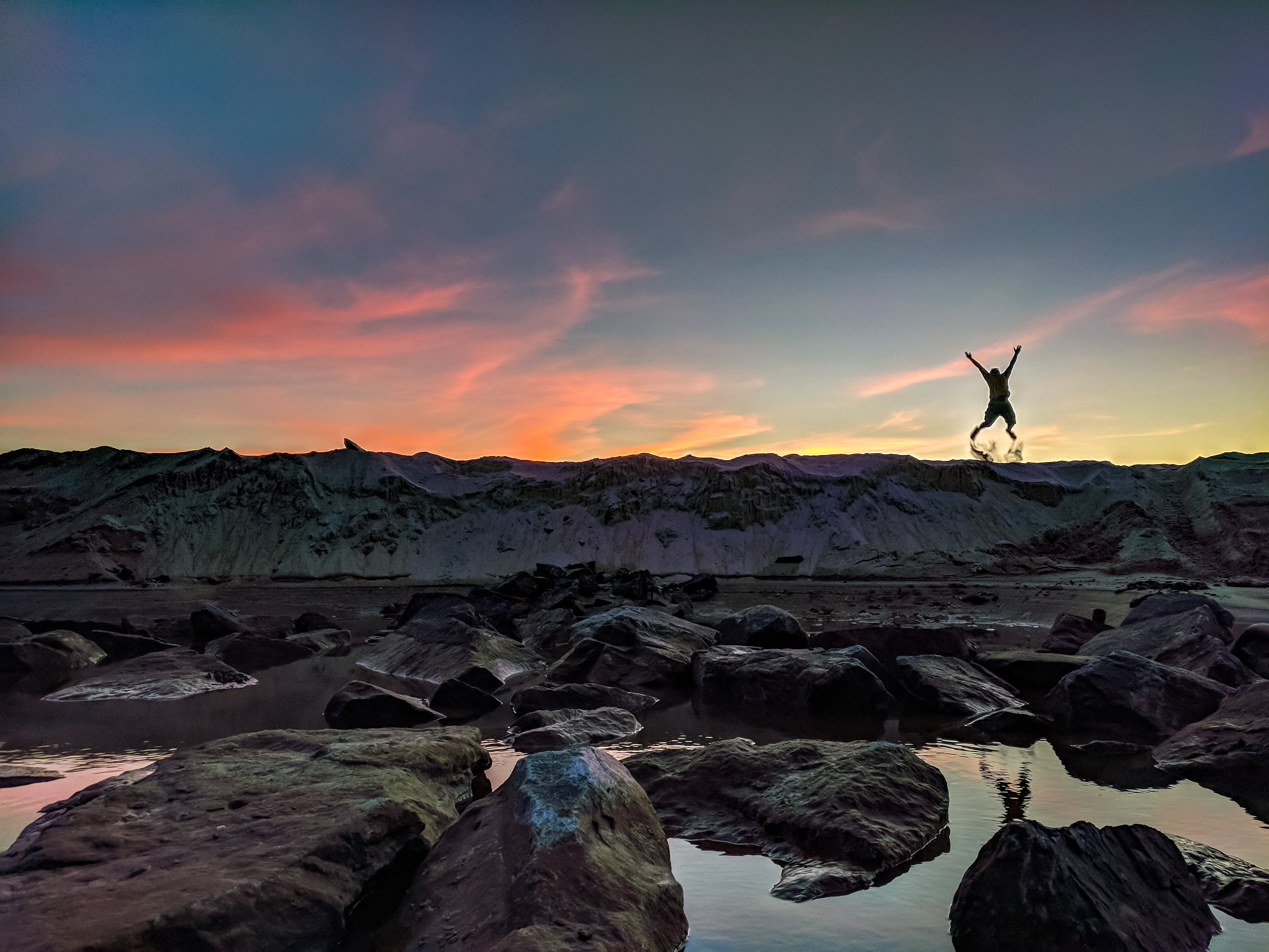 Person Jumping on Mountain Photo