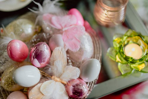 From above of shiny Easter eggs in bowl with decorative artificial butterflies placed on glass table with small candle