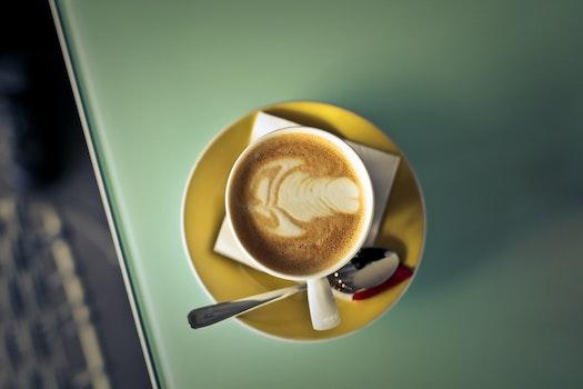 Coffee Latte on Saucer Beside Spoon