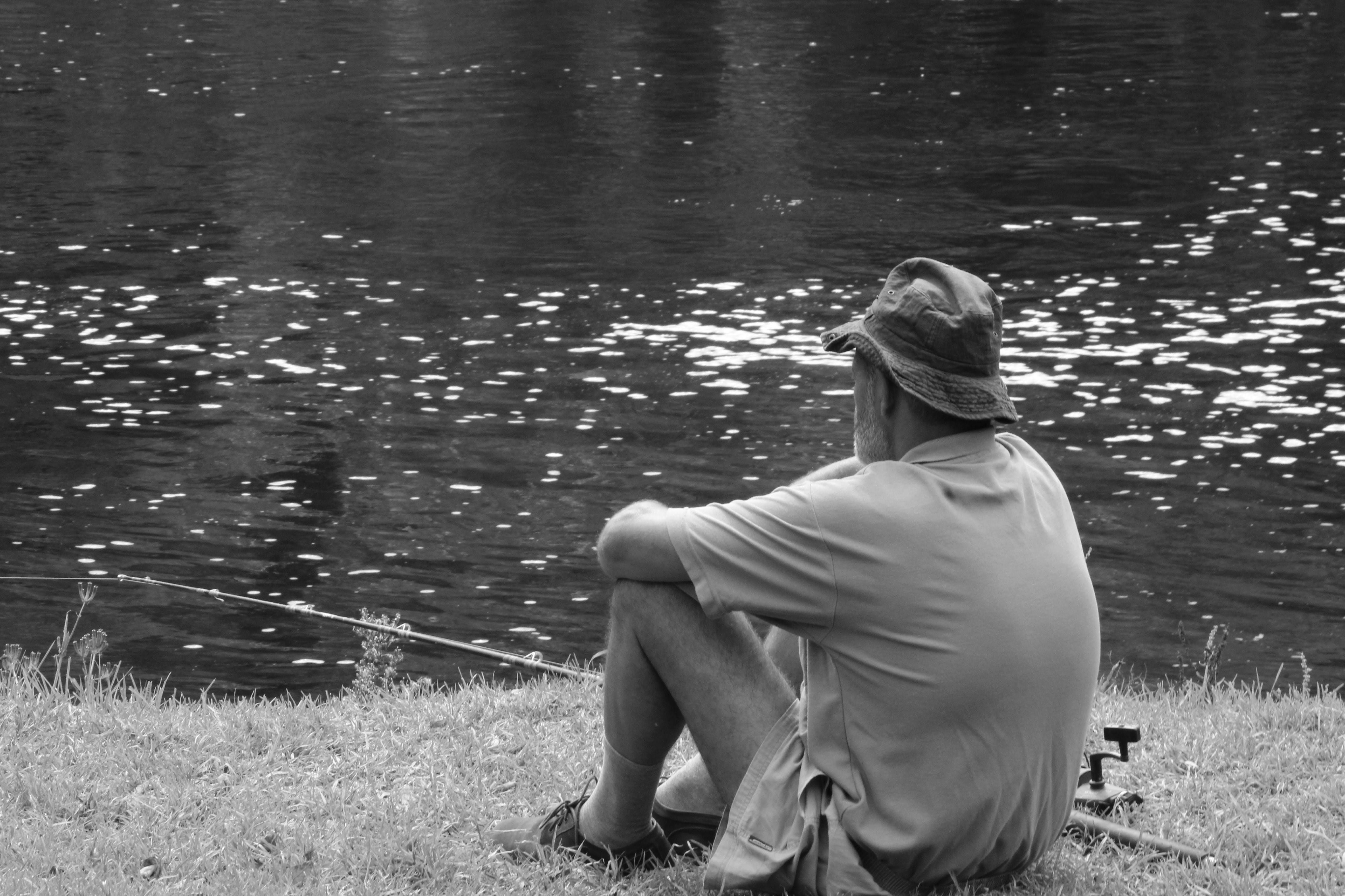 Man Sitting Facing Body Of Water