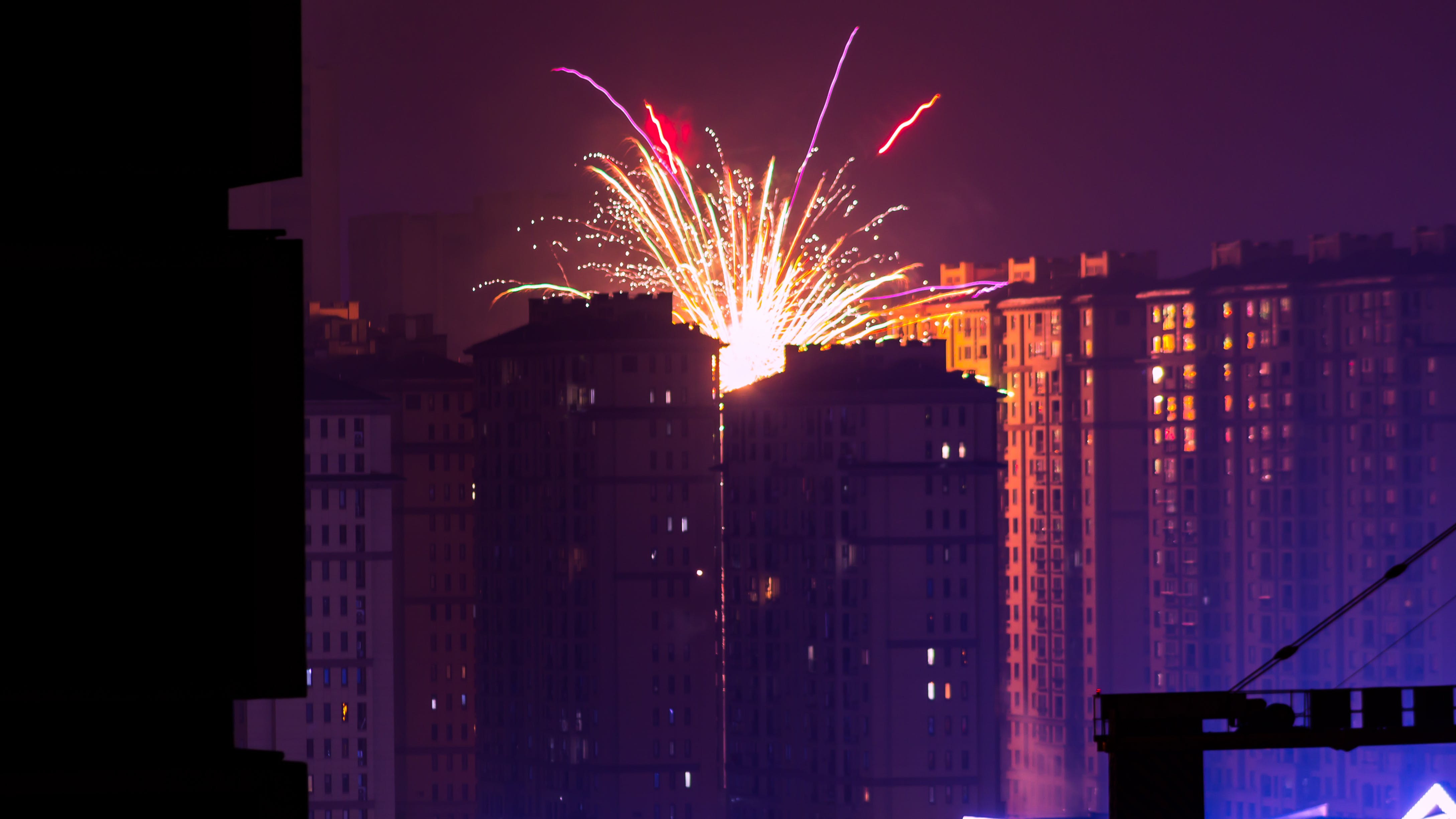 Fireworks Display Near High Rise Buildings during Nighttime