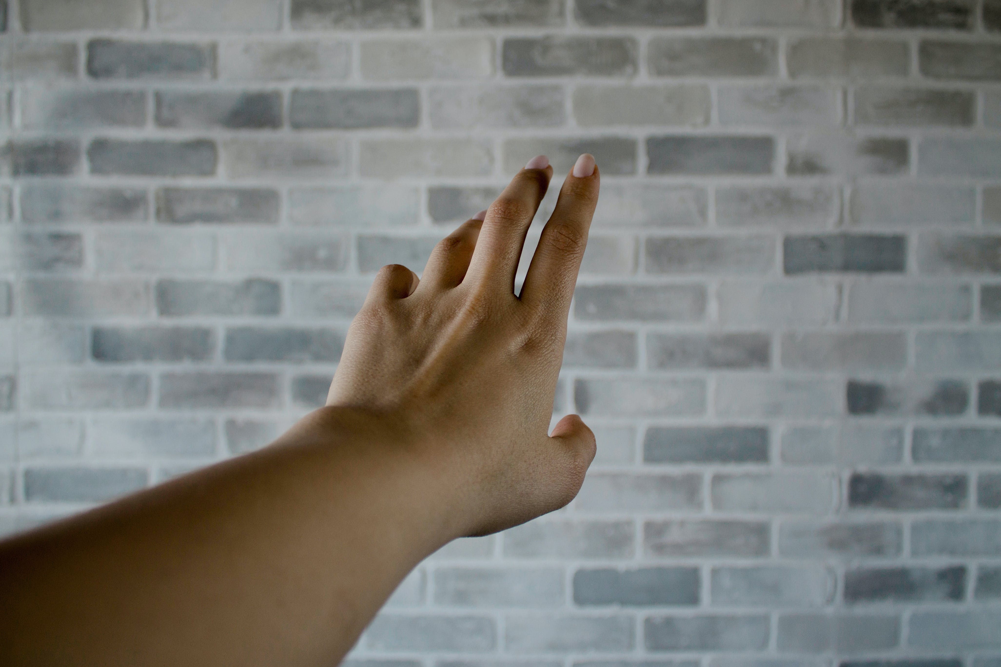 Person's Left Hand Near Gray Cinder Bricks