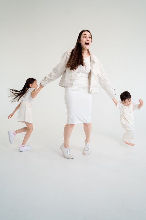 Woman in White Blazer and White Dress Shirt Holding Girl in White Dress