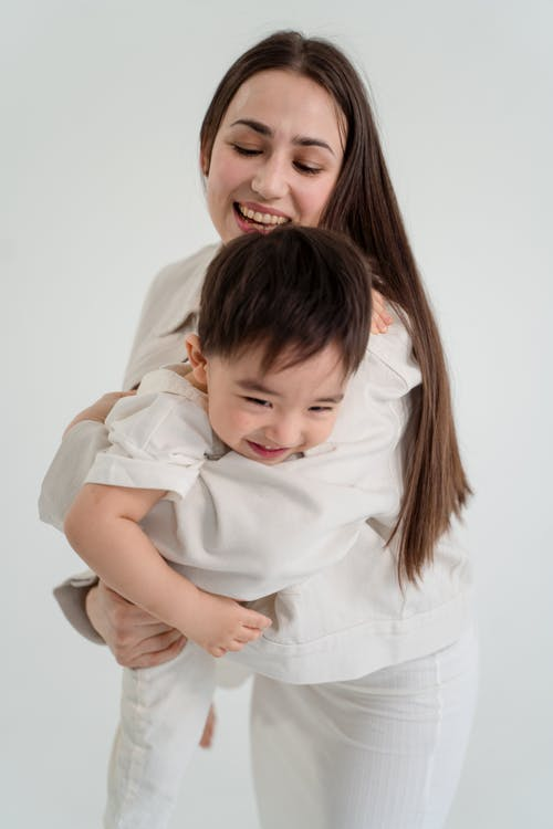 Woman in White Dress Shirt Carrying Baby in White Dress