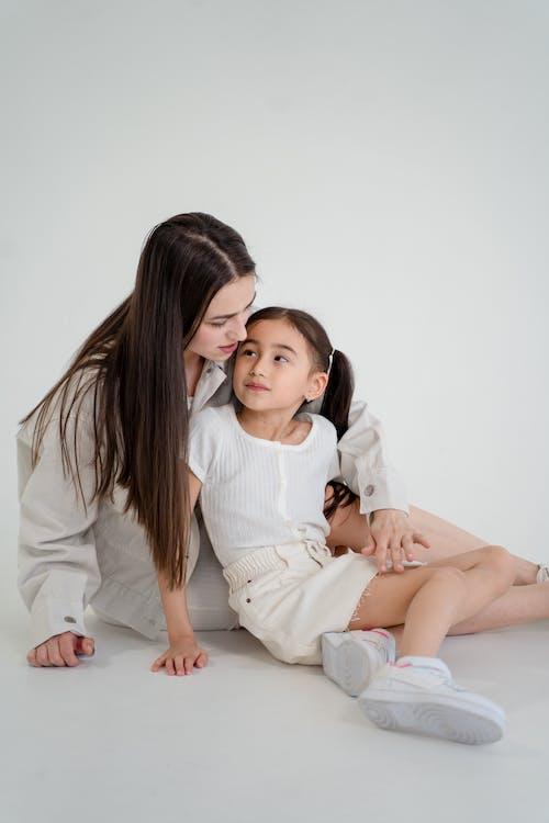 Eine Mutter Und Eine Tochter, Die Auf Dem Boden Sitzen