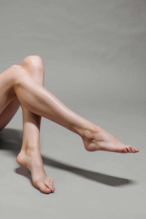 Woman in White Stockings Lying on White Floor