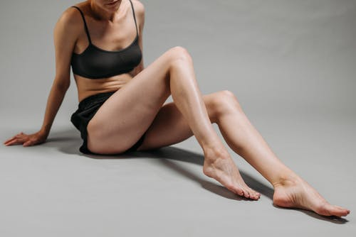 Woman in Black Sports Bra and Black Shorts Sitting on White Floor