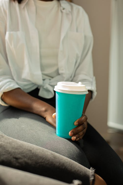 Close-Up Photo of a Person Holding a Turquoise Cup