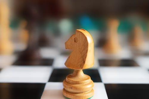 Selective Focus Photo of a Wooden Knight Chess Piece